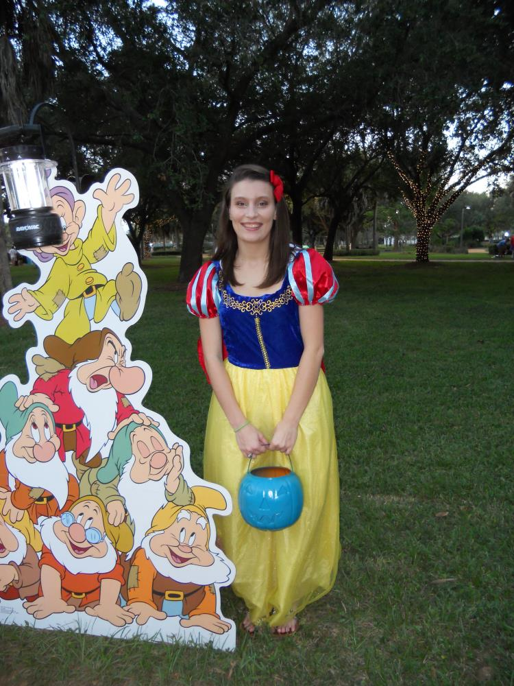 Young woman dressed as Snow White standing next to cardboard cutout of the seven dwarves