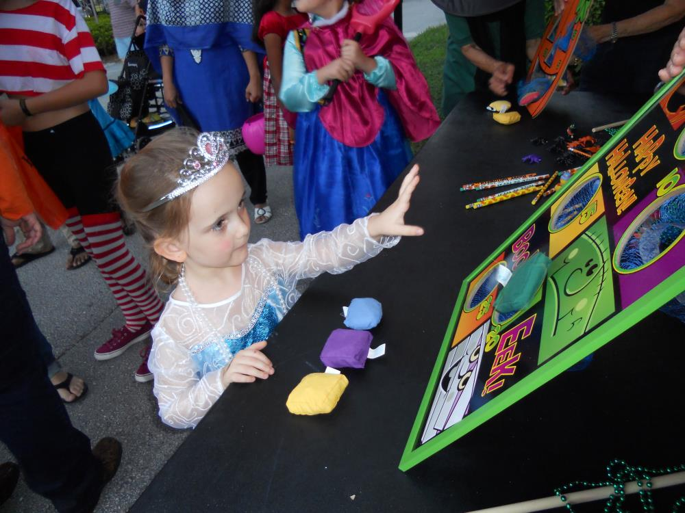 Girl dressed as Elsa trying to throw bean bags through holes in cardboard rectangle on table