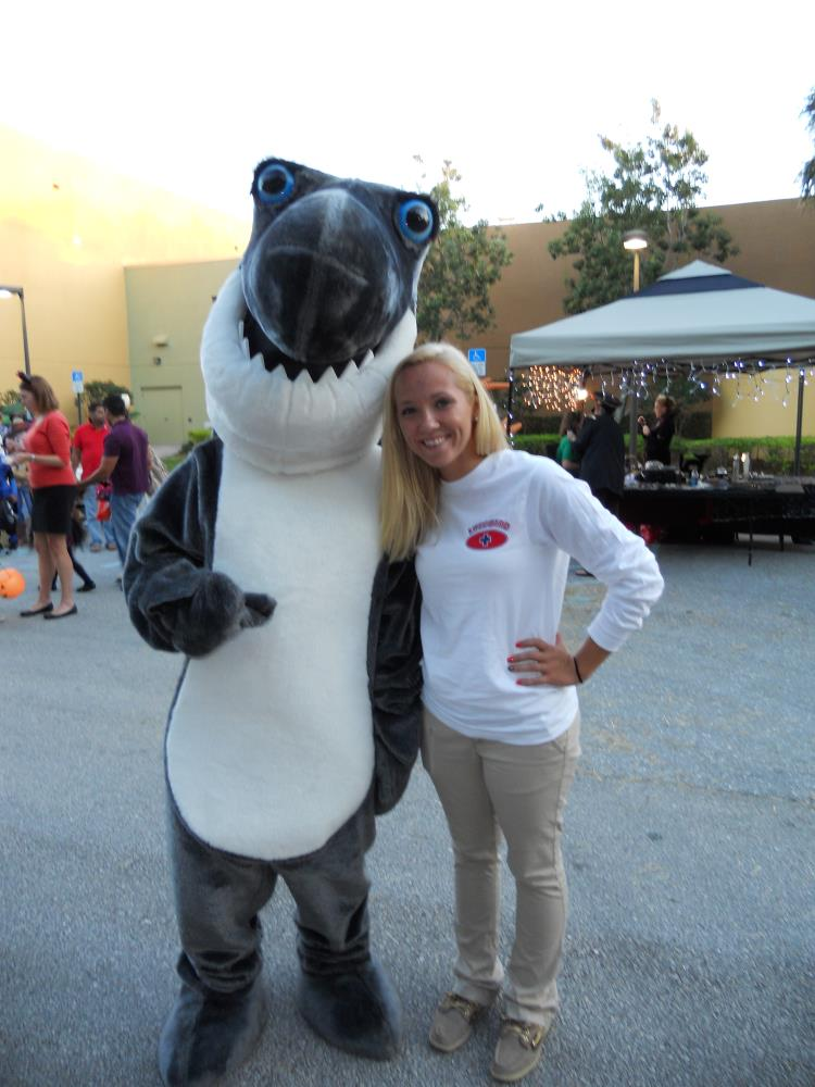 Person dressed in shark costume stands next to young woman