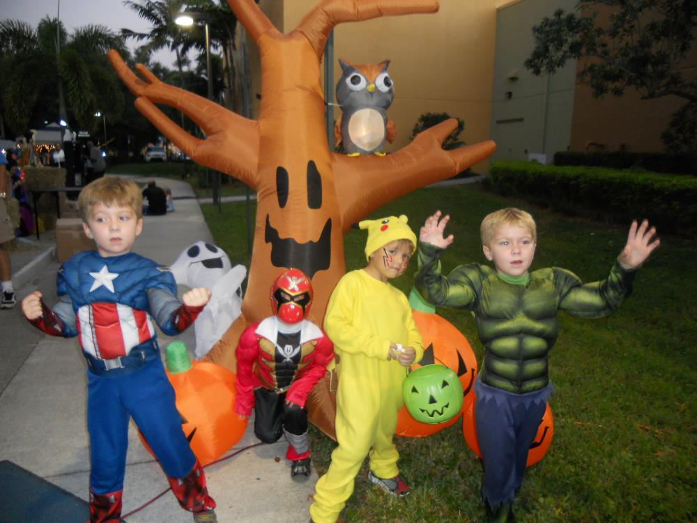Kids dressed as Captain America, red Power Ranger, Pikachu and The Hulk stand in front of inflatable Halloween tree and inflatable jack-o-lanterns