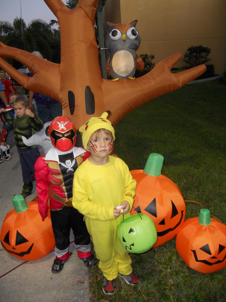 Child dressed as red Power Ranger and kid dressed as Pikachu standing in front of inflatable Halloween tree and inflatable jack-o-lanterns