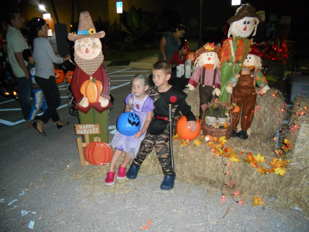 Girl in purple princess outfit and blue jack-o-lantern bucket sitting on hay bales next to boy in black and camouflage ninja outfit