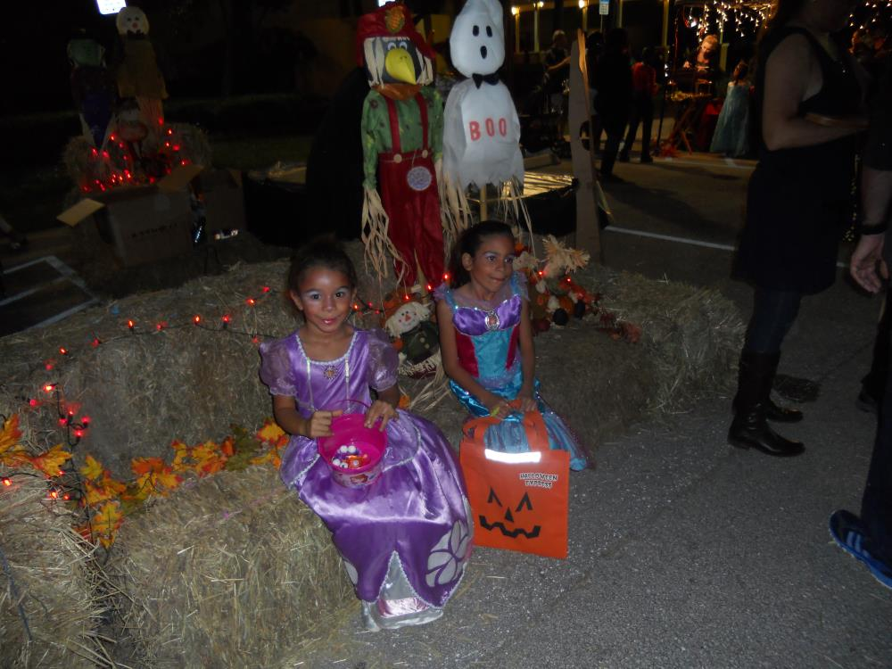 Girl in purple princess costume holding pink candy bucket sits on hay bales next with girl in blue princess outfit holding orange jack-o-lantern candy bag