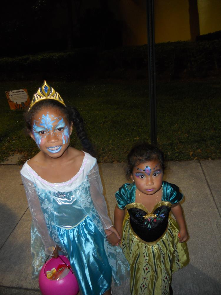 Girl with blue face paint and blue princess costume holding hands with younger girl in princess costume