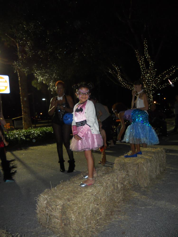 Girl in pink batman costume and white coat standing on hay bales