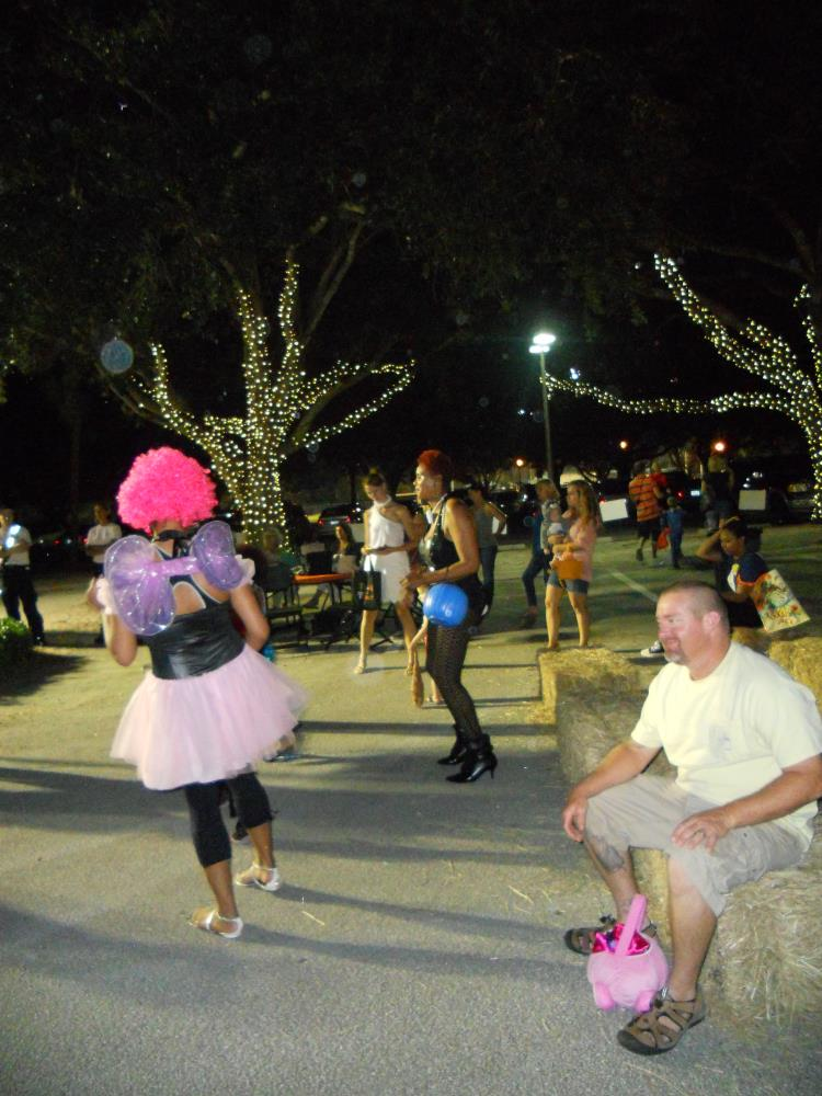 People in Halloween costumes dance in street