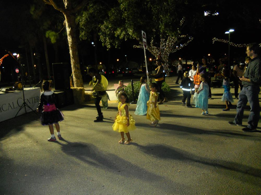 Children in Halloween costumes dance in front of band stage