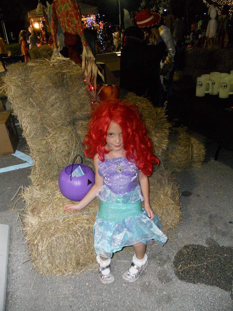 Girl dressed as Ariel from The Little Mermaid sitting on hay bales