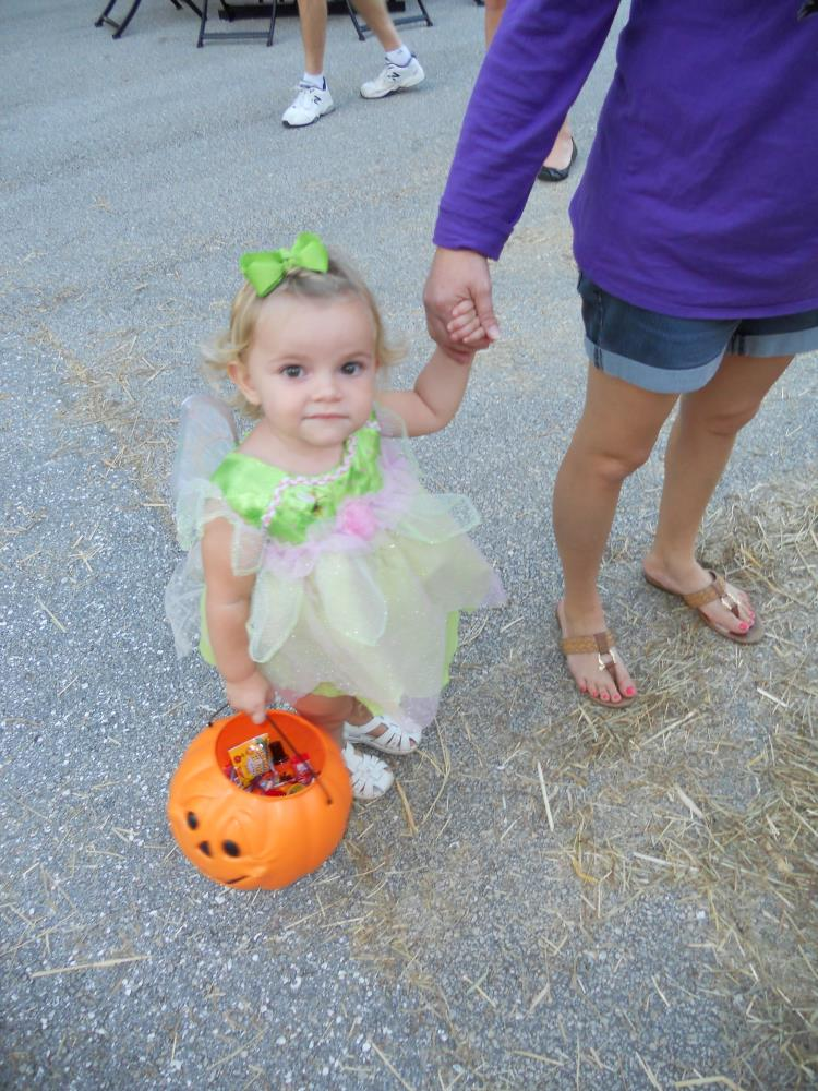 Young girl dressed in bright green and pink dress holding woman's hand and orange jack-o-lantern bucket