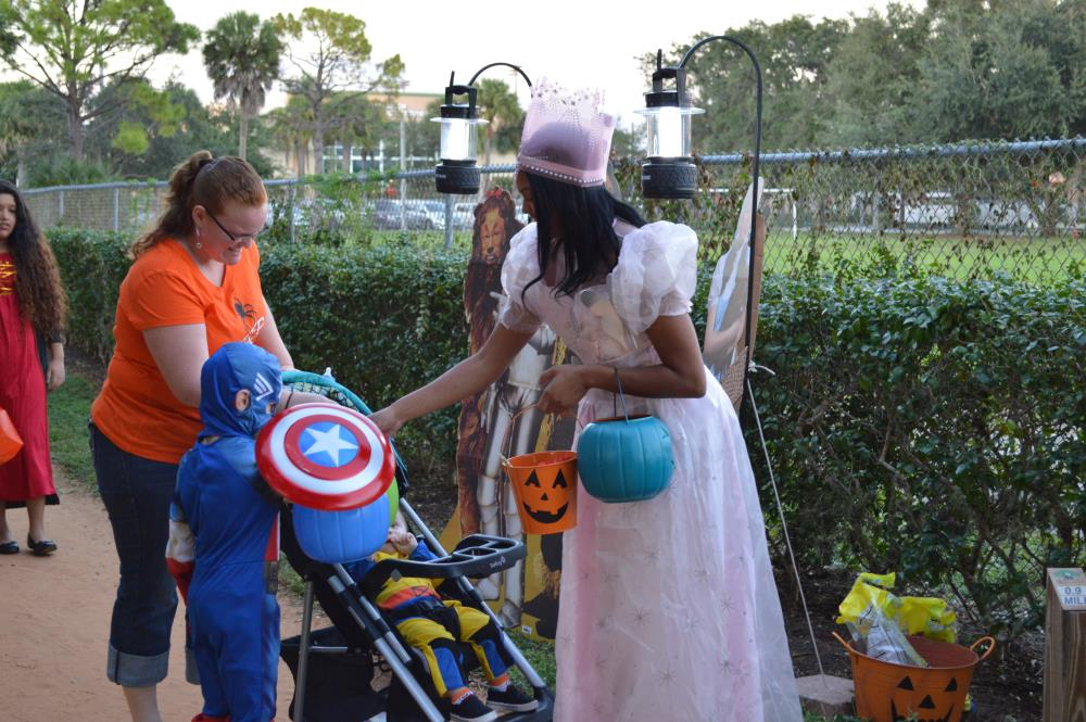 Young woman dressed in pink dress hands candy to boy dressed in Captain America costume