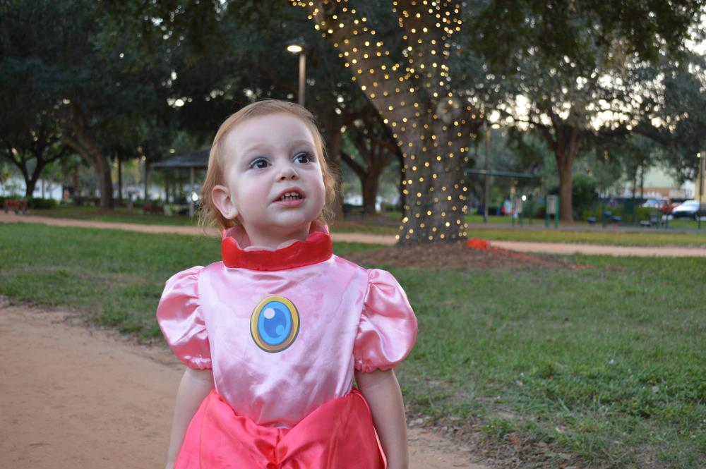 Young girl in pink princess outfit with tree wrapped in lights in background