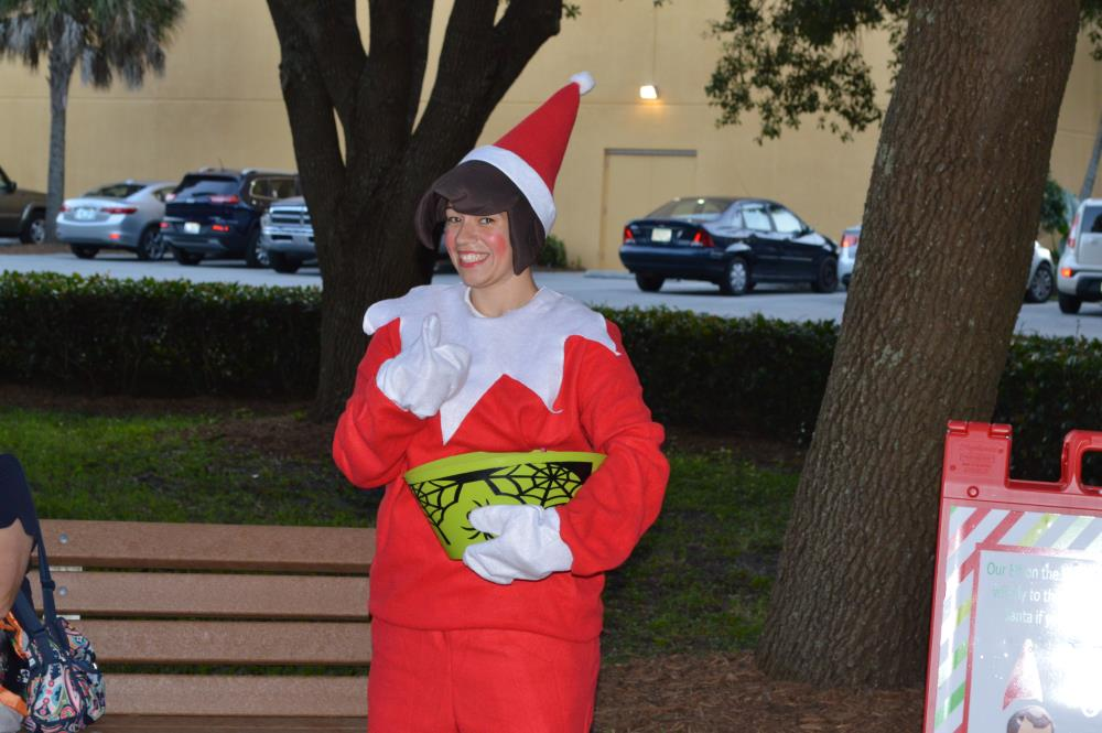 Woman in red elf costume gives a thumbs up and smiles to camera