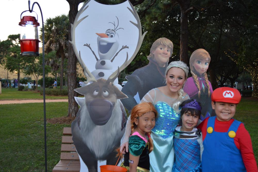 Young woman dressed as Elsa poses for picture with girl dressed as Merida from Brave, girl in blue dress and boy dressed as Mario in front of Frozen character cutouts