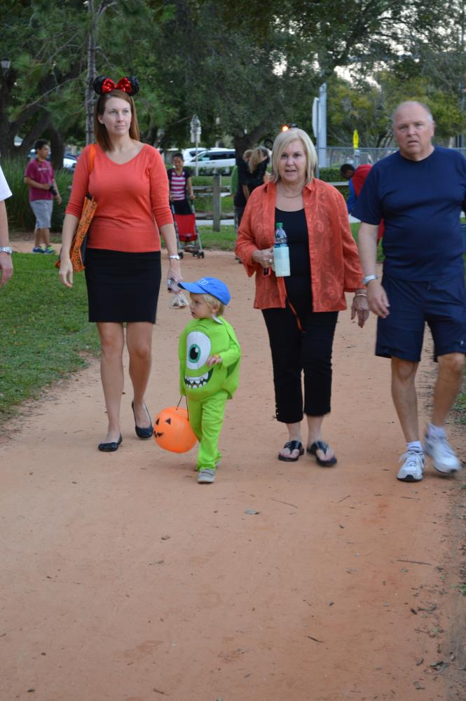 Kid dressed as Mike Wazowski carrying orange jack-o-lantern walks with adults