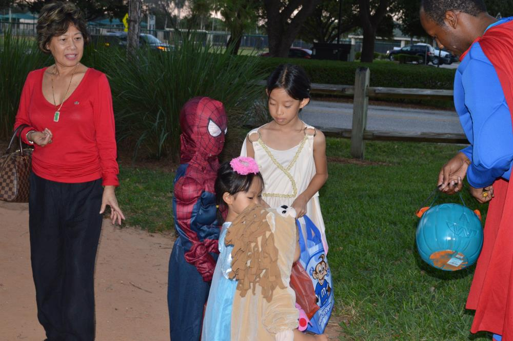 Kid dressed as Spiderman stands with girl dressed in Greek-style dress, girl dressed in blue princess outfit and child dressed as lion and man dressed as Superman