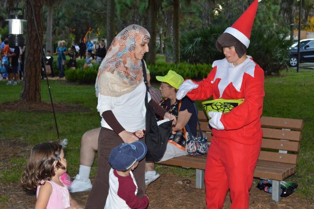 Woman in red elf costume hands out candy to kids