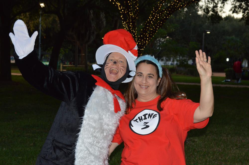 Woman dressed as the Cat in the Hat waves to camera with woman dressed as Thing 3