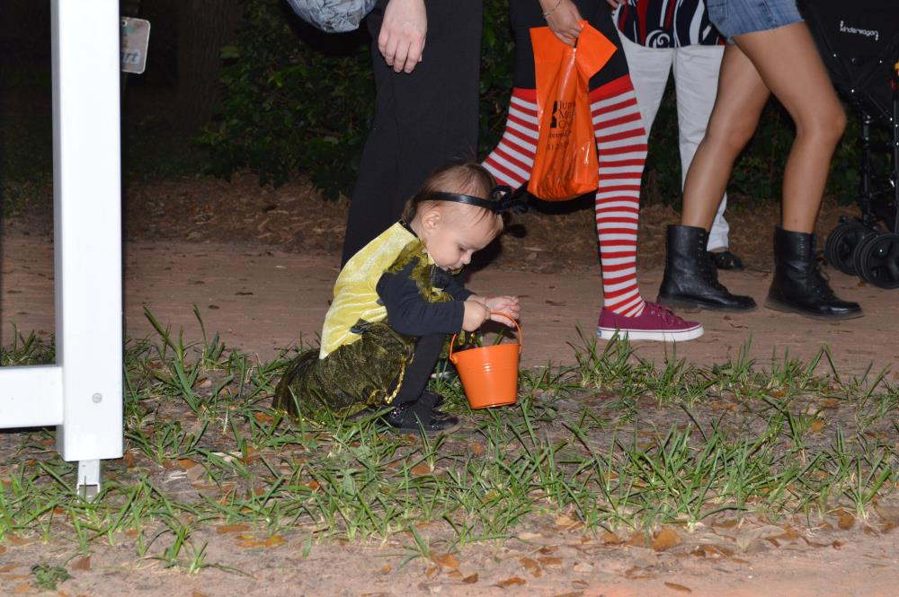 Young girl in yellow costume picking grass and putting it in orange pale