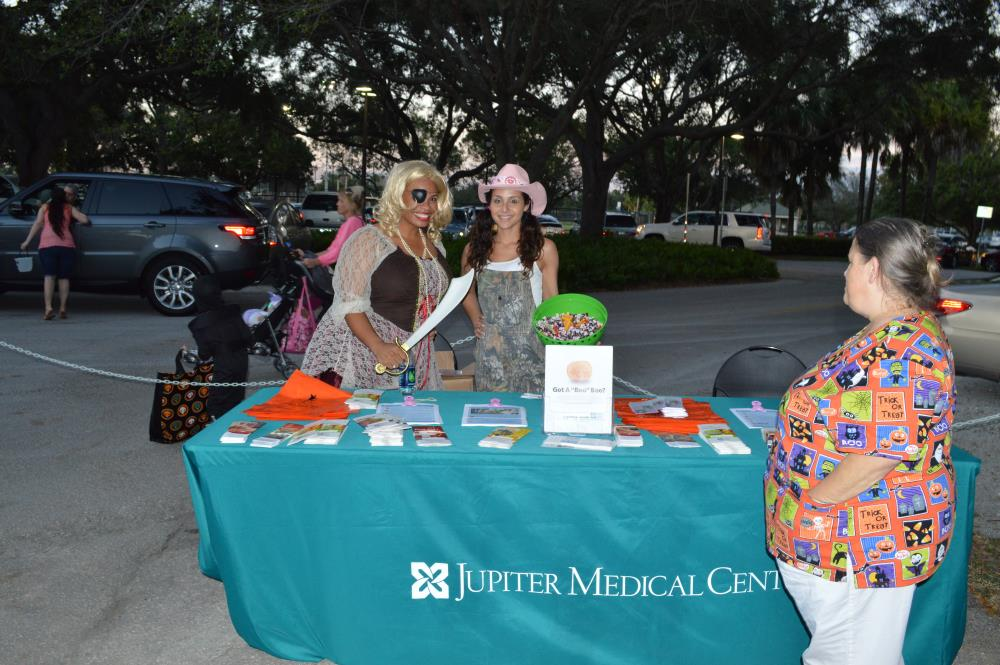 Woman dressed in pirate costume stands next to woman dressed in camo overalls and pink cowgirl hat behind Jupiter Medical Center information booth