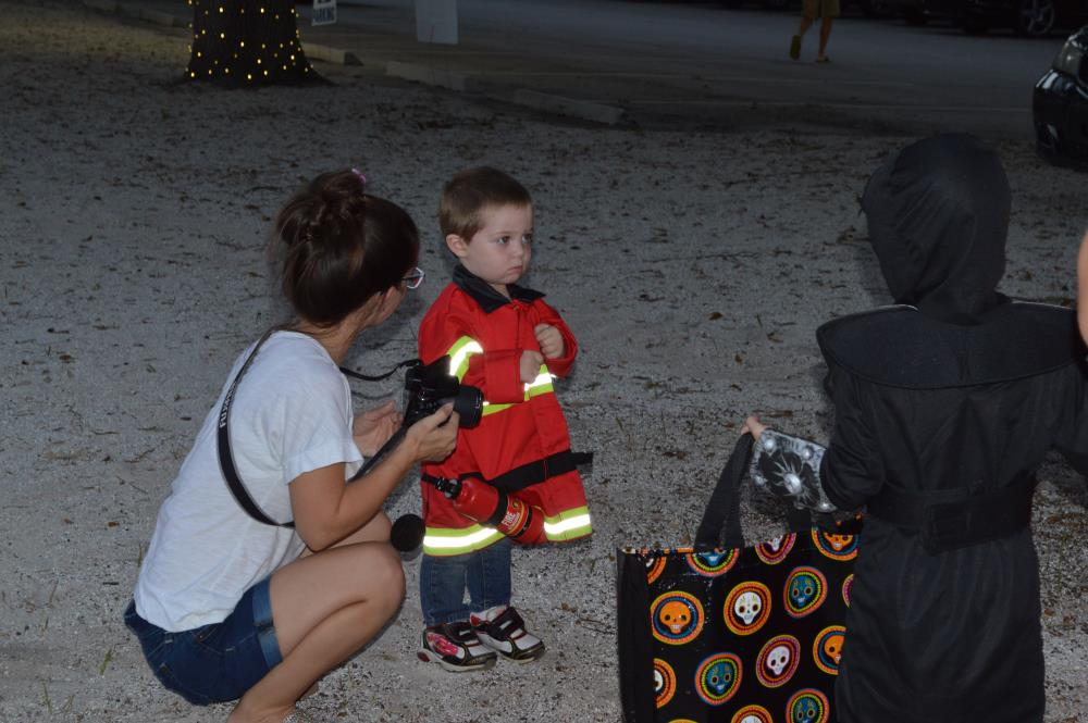Woman with camera talks to boy dressed in red firefighter costume