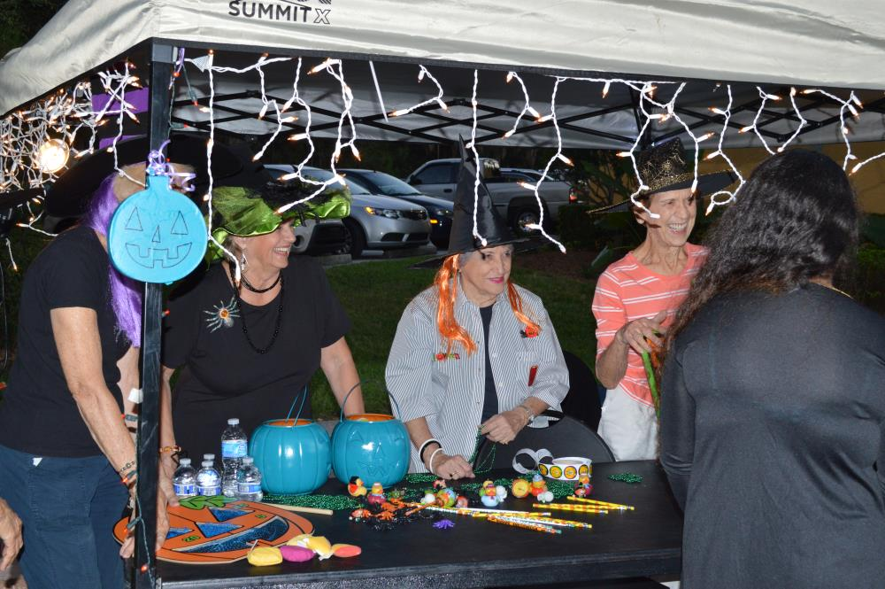 Women wearing witch hats stand behind table with Halloween-themed toys and items