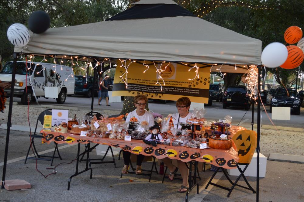 Two women sit behind table with jack-o-lantern-themed table cloth with various food items for sale