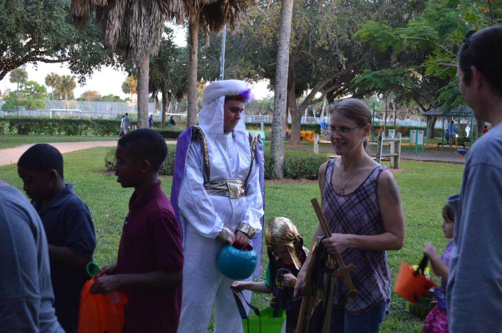 Person dressed as a sultan holding blue jack-o-lantern candy bucket