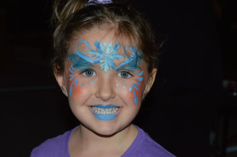 Girl smiles for camera with blue facepaint design on face