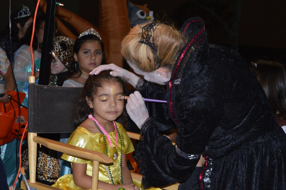 Girl in yellow dress from Beauty and the Beast gets face painted by woman in black dress