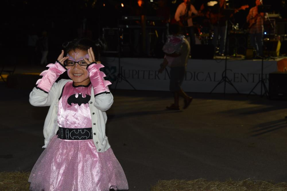 Young girl in pink batman dress and white coat