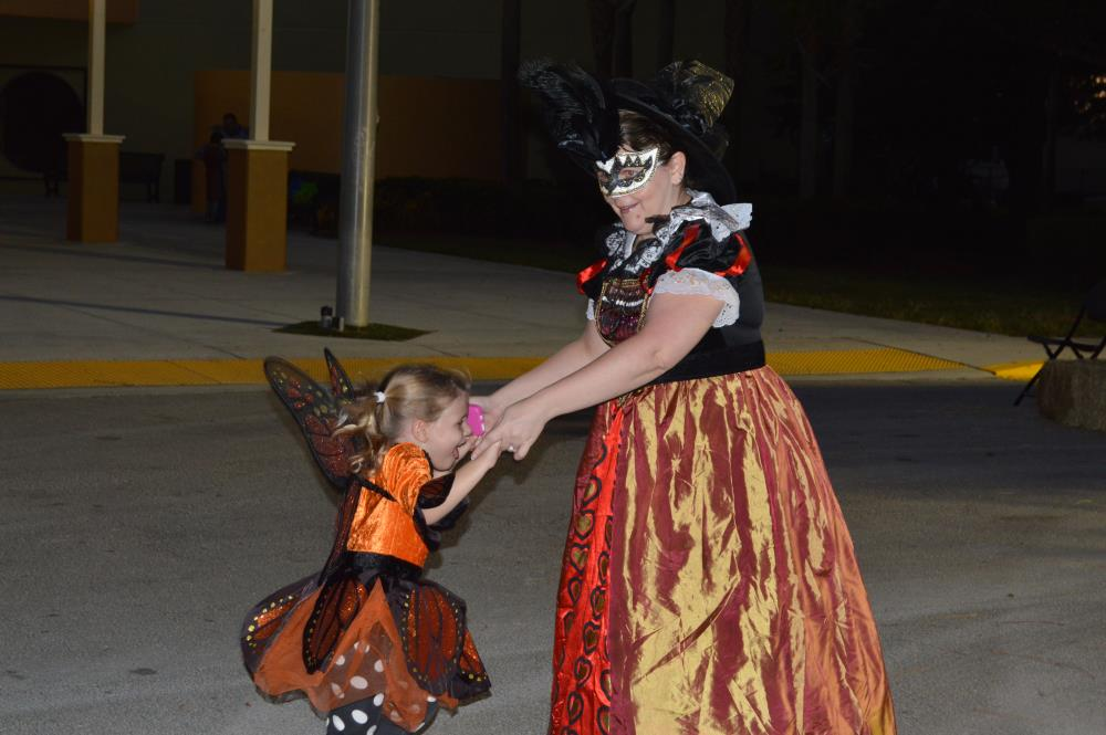 Woman in intricate dress and mask dances in street with girl in monarch butterfly dress