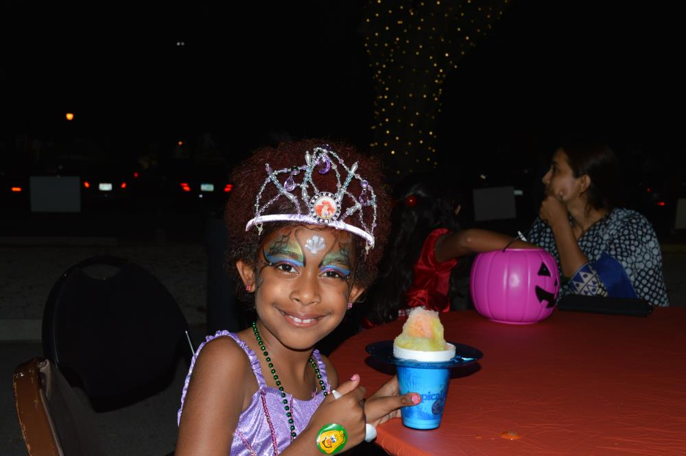 Girl with purple dress and Little Mermaid-themed crown shows snow cone