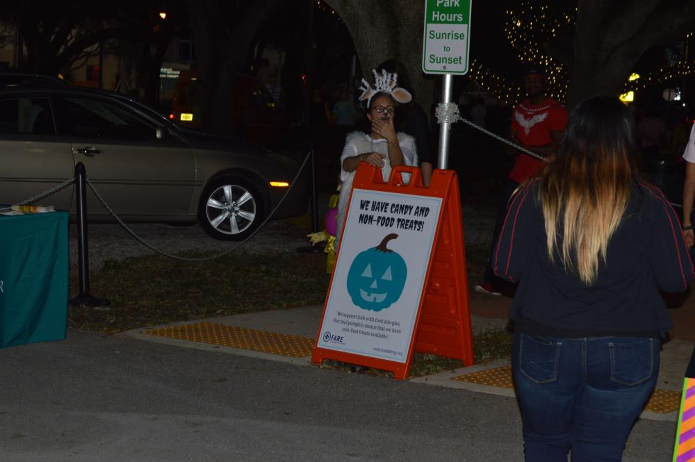 "Person in lamb costume stands next to sign with text ""We have candy and non-food treats"" and image of blue jack-o-lantern on sign"