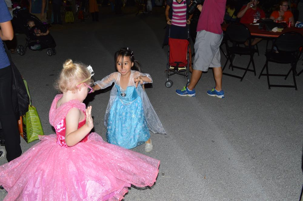Girl dressed in blue dress and girl dressed in pink dress play