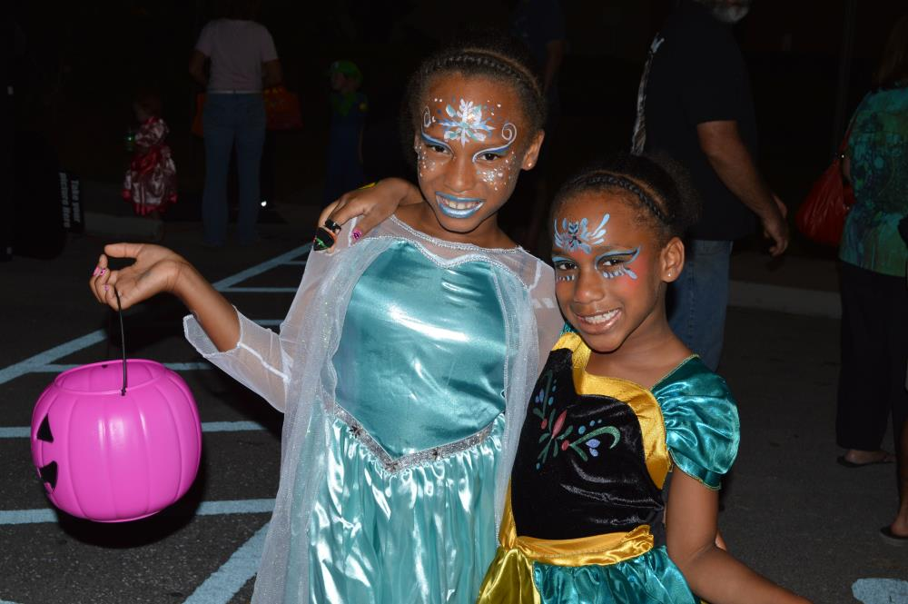 Two girls dressed as princesses, one holding plastic, pink jack-o-lantern